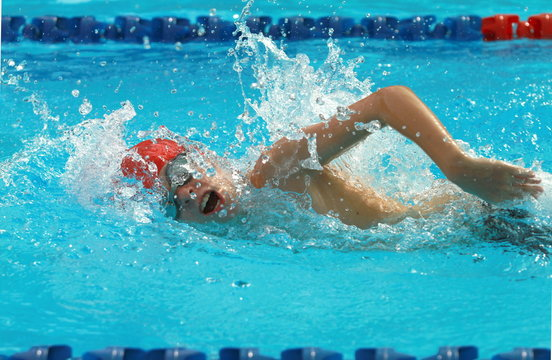 Young swimmer wearing red cap practice forward crawl swimming stroke in a swimming pool