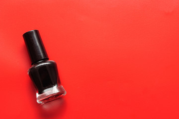 A bottle of black nail polish isolated on a red background