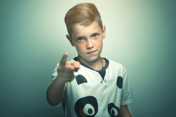 Angry teenage boy pointing with finger to you. Isolated against white grey background.