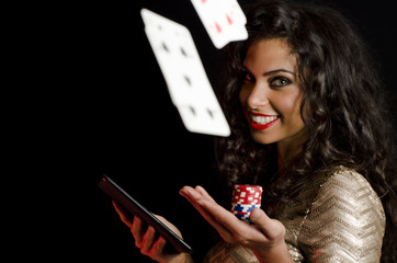 Cards flying in air, while girl holding poker chips and tablet