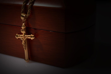 gold cross and chain top on a wooden box, copy space