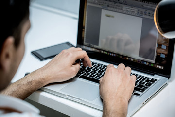 Hands typing on computer in an office