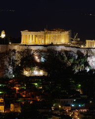 Athens Greece, night view of Parthenon and Plaka old neighborhood