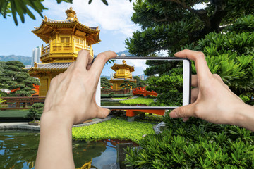 A tourist using smartphone camera to take a picture of the Pavilion of Absolute Perfection in Nan Lian Garden, Chi Lin Nunnery in Hong Kong