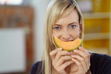 lachende frau mit einem stück honigmelone