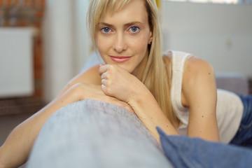 junge frau mit blauen augen sitzt entspannt auf dem sofa