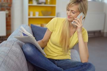 frau schaut in die tageszeitung und telefoniert