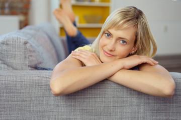 verträumte junge frau liegt auf dem sofa