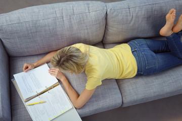 frau liegt auf dem sofa und liest in den unterlagen