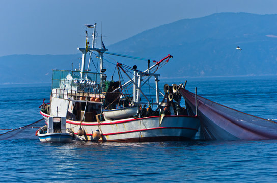 Fishing boat with nests at sea in front of mountain Athos, Greece