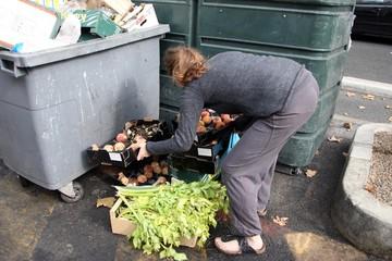 Une jeune femme étudiante récupère des fruits et legumes jetés dans les poubelles par des primeurs apres un marché