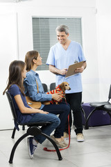 Nurse Holding Form While Looking At Family With Ill Dachshund