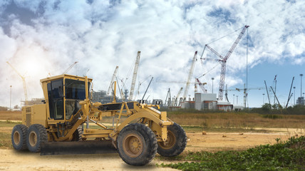 Grader and building construction site against blue sky
