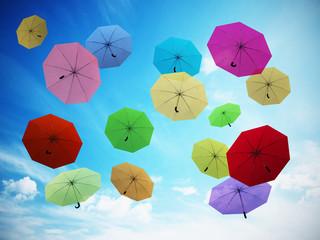 Multi colored umbrellas against blue sky. 3D illustration