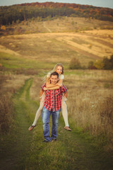 Man in jeans and red plaid shirt carries his woman across the fi
