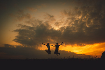 Young couple hold their hands tightly while jumpung under golden