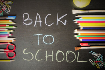 "School supplies on blackboard background with text ""back to school"""