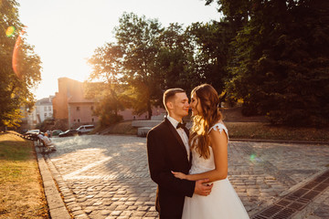 Evening sunlight illuminates lovely wedding couple standing on t
