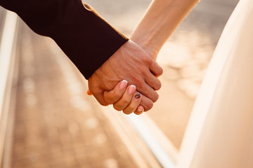 Closeup of newlyweds hands holding each other hands in the rays