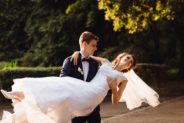 Young groom whirls elegant bride in the park