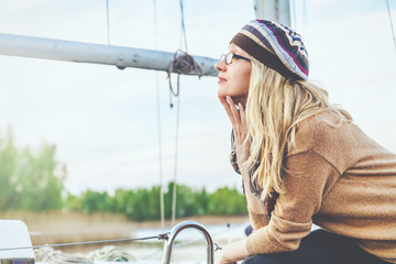 Blonde in sunglasses against backdrop of mast yacht