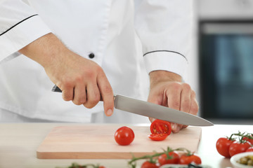 Chef cutting tomato on wooden board in kitchen