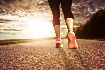 Joggen in pinken Laufschuhen auf asphaltierter Strasse - Der Sonne entgegen