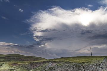 the sun shines through the big storm cloud