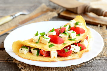 Home stuffed omelet on a plate. Egg omelet with a filling of fresh cherry tomatoes, cheese and parsley. Simple vegetarian breakfast recipe. Fork, knife, cutting board on wooden background. Closeup