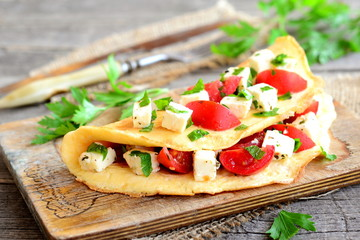 Delicious stuffed omelette on a wooden board. Fried egg omelette with a filling of cherry tomatoes, cheese and parsley. Easy cooking breakfast. Fork, knife, parsley sprigs on wood background. Closeup