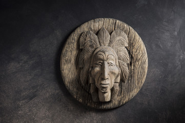 still life photography : old wood carved of indian chief head on dark background