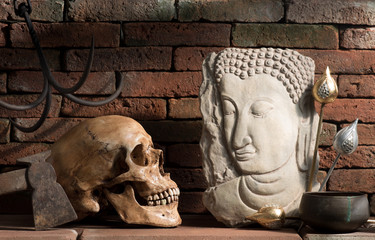 Still life photography : eye contact between buddha image and skull in good and evil concept