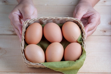 hand holding egg on wooden background
