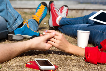 Dating Couple relaxing on lawn in modern City