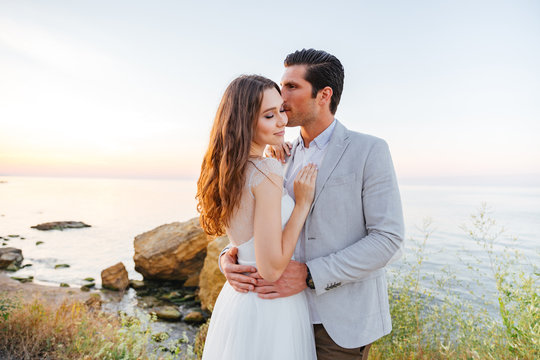 Romantic married couple kissing on the beach