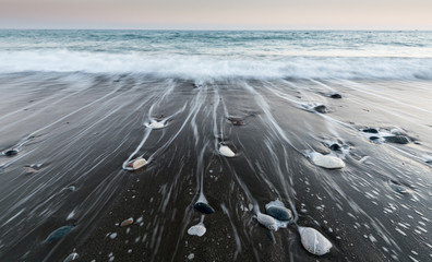 Photo sur Plexiglas Zen pierres a sable Pebbles in the beach and flowing sea water