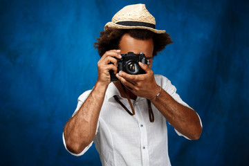 Young handsome african man taking photo over blue background.
