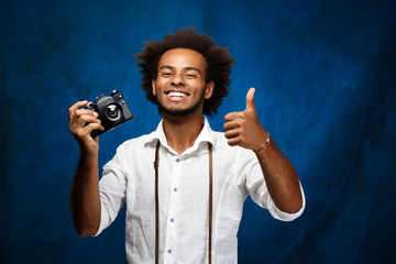 Young handsome african man holding old camera over blue background.