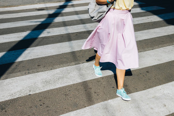 Girl in a pink skirt and sneakers crossing the road in the summe Wall mural
