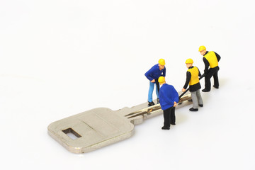 Group of locksmith workers are making the key isolated on white