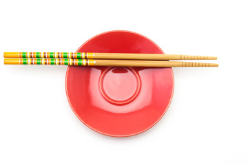 Plate with chopsticks on white background