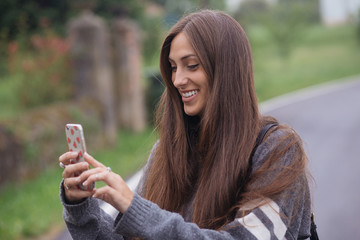 Pretty smiling woman makes photo with her phone
