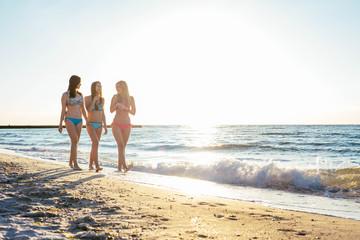 three girls having fun on beach, friends on beach in sunset light