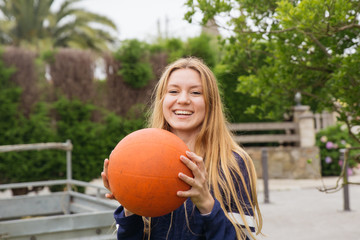 Young Blond Woman Holding a Basketball Ball