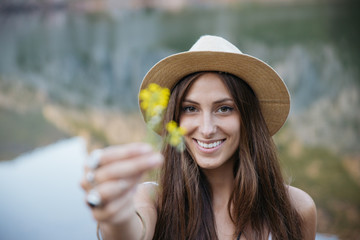 Happy young brunette woman holding yellow defocused flower