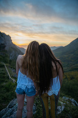 Two girlfriends looking forward on mountain sunset
