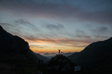 Tourist with arms up at dusk in mountains