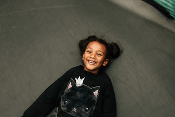 Portrait of little girl lying on the floor and laughing