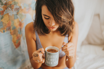 Portrait of mulatto woman wearing underwear in bedroom with cup of coffee