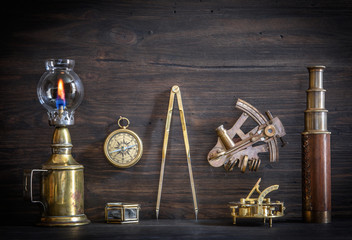 Wall Mural - Overhead view of pirate or sailor gear laid out for a backpacking trip on a old wood floor. Items include, rope, compass, money, binoculars, sextant , shell. Stories background.